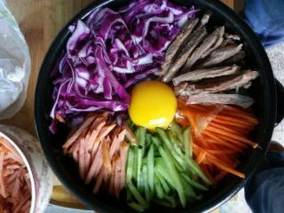 石锅拌饭,把胡萝卜,牛肉,火腿肠还有黄瓜,紫甘蓝切细丝,整齐的码在米饭上面