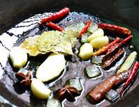 黄豆焖猪蹄,炒锅内放油,油温后将冰糖、姜蒜、桂皮、八角、香叶、辣椒段以小火炒至料香糖化。