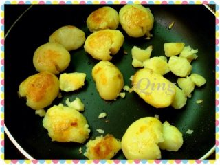 香辣小土豆,如图将煮熟的土豆放入锅里中火,用菜勺把土豆压扁煎至两面金黄时,关小火放入辣椒粉孜然粉和盐,再滴入几滴酱油散入少量葱花翻炒均匀