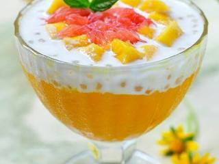杨枝甘露,取芒果泥铺在杯底2/3满,再装上1/3量的西米椰浆汁,在表面撒上芒果粒及西柚粒即可,食用时用汤匙搅拌均匀。