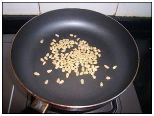 老少皆宜的夏日爽口菜—松仁番茄,去壳松子仁放入平底锅中,用小火烘焙出香味,取出切碎。
