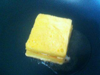 芝士火腿西多士,锅烧热,倒入适量的食用油,小火,将制作好的半成品裹上蛋液置入锅中