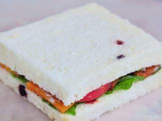 蔬菜总荟三明治,将两片面包重叠在一起,按压几秒,用刀对角斜切开即可。