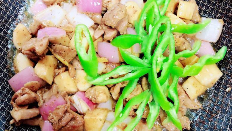 杏鲍菇炒鸡丁,放入尖椒丝,翻炒入味。
