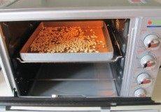 秋意浓,坚果香----松子饼干,先将松子平铺在烤盘上;
