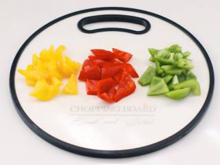 彩椒鸡腿饭,把青椒和红椒,黄椒去籽后用刀切小块。