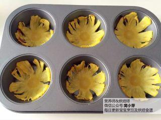 宝宝辅食:天然健康又美美的烤菠萝花:面向,把步骤5中的菠萝片稍冷却后移至玛芬模具,让菠萝片形成立体花朵的感觉。