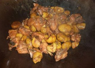 板栗焖鸡,加入板栗和水,盖上锅盖,焖至水分将干时,加入适量的盐炒匀,撒上葱粒即可上碟。