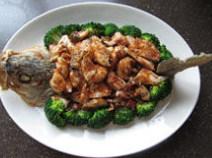 香辣鲈鱼,捞出沥油,盘中摆放鱼头、鱼尾、鱼肉和鱼骨,用熟西兰花围边