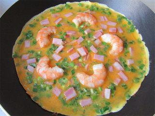 虾仁韭菜厚蛋饼,每次凝固一层再倒一层蛋液,并在第二层时铺上培根丁和虾仁