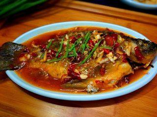 家常烧鲫鱼,将调好的料稠汁儿浇在鱼身上面,撒上葱叶即可