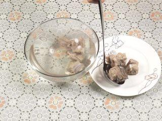 胡萝卜玉米排骨汤,洗干净后,捞出排骨放入盘子中沥干水份。