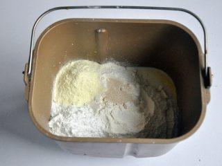 黄油椰蓉吐司条,把液体材料放入面包桶中,面粉铺在上面,对角分别上放上盐、糖、奶粉,在面粉中间挖一个小坑,放上酵母,启动面包机揉面程序10分钟。