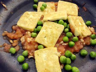 宝宝辅食:西红柿烧豆腐-18M+ ,放入步骤2中准备好的豌豆和煎好的豆腐,中小火简单翻炒,然后稍稍放一点点盐炒匀,继续翻炒1分钟左右即可出锅。