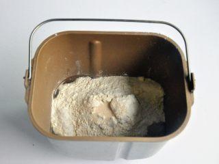 口袋三明治, 把液体材料放入面包桶中,面粉铺在上面,对角分别上放上盐、糖、奶粉,在面粉中间挖一个小坑,放上酵母,启动面包机揉面程序10分钟。