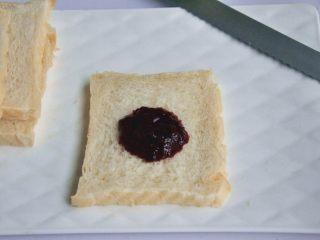 口袋三明治,出炉后立即脱模,在晾架上散热,取出后最好先侧放一会儿,以免凹腰,待完全凉透再切片,取一片吐司,抹上草莓桑葚酱。