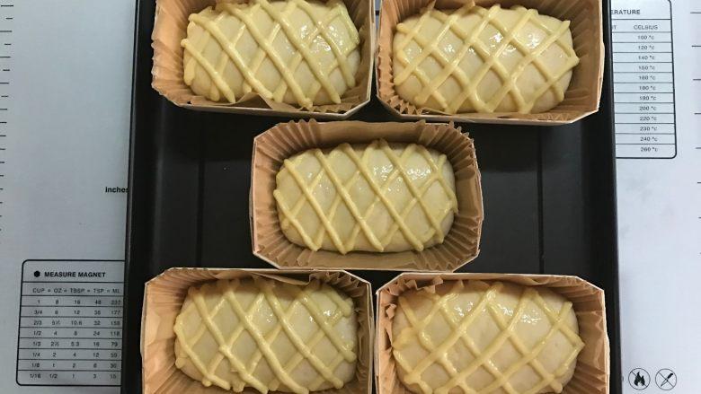 黄桃香酥面包,表面刷蛋液,卡仕达酱挤成菱形状。