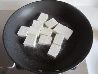 雪菜肉末烧豆腐,烧热锅,放少许油, 将切成小块的豆腐下去煎;