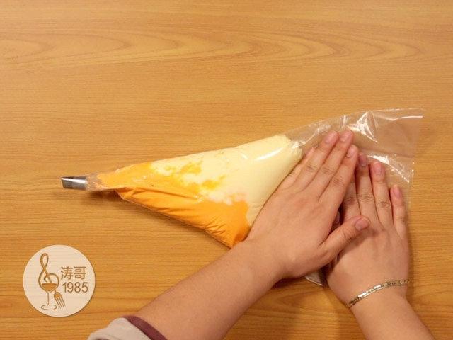 黄桃裙边蛋糕,都装好后把裱花袋放在桌子上压一压,压出多余的气泡后拧紧放一旁备用