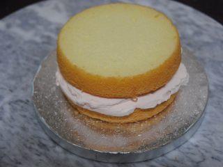 巧克力淋面蛋糕,放一片蛋糕片在底座上,抹上淡奶油,加入蜜豆,抹平后盖上一层蛋糕片