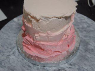 巧克力淋面蛋糕,剩余的淡奶油加入细砂糖和一滴红色素打发,取1/3抹在最上面层,剩余的再加入一点点红色素混匀,取出抹在蛋糕边上