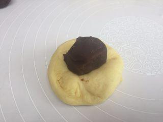 花朵豆沙面包,取一个面团,揉圆,把豆沙放在面团的中间,用虎口,收口;