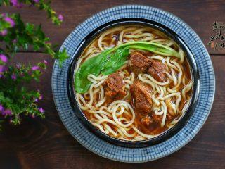好看更好吃的红烧牛肉面,然后把面条下锅煮熟,碗中备好牛肉汤,把面捞到汤中,再加几块牛肉,烫点儿青菜也放进去。