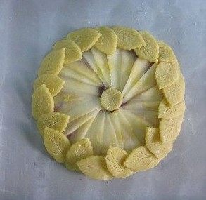蓝莓奶酪苹果派】,中间摆上一小圆形派皮,再将刻好的叶子沿着四周围上一圈,底边稍压紧一下