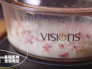 灵魂猪油菜饭, 将洗好的米,水,咸肉和腊肠切丁放入锅中,再加入一些熬好的猪油,盖上锅盖,开始焖煮。