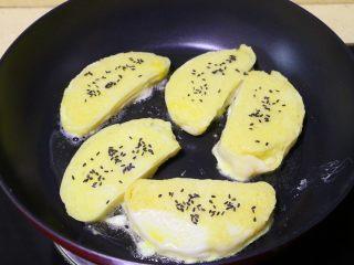 蛋煎馒头片,每片馒头片上撒上少许黑芝麻,小火慢煎