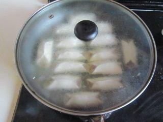 西葫芦肉馅锅贴,盖上盖, 稍微煮上三、四分钟, 揭开盖, 大火收汁;