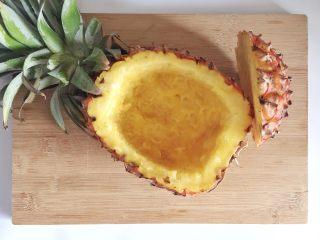 粗粮凤梨炒饭,凤梨皮留出厚度约2厘米,用刀和勺子把内部掏空,取出凤梨肉,制成凤梨碗。