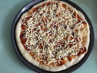 大虾披萨,烤好后取出饼,表面刷一层披萨酱,撒上马苏里拉芝士碎。