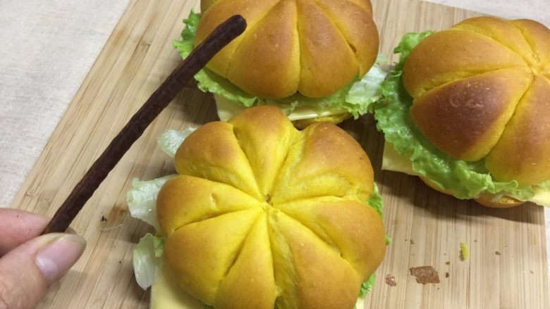 南瓜汉堡包,最后用巧克力棒从中间把整个面包串起来,一来可以固定整个汉堡,二来顶部突出一点点可以假装是南瓜瓜蒂