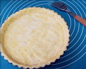 肉桂苹果派,铺在派盘上,用手轻轻按一下四边,然后用擀面杖沿着边缘擀掉多余的面皮。用叉子在派皮上扎一些孔