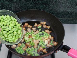 五花肉蒜香腊味焖饭,加入豆角炒至皮起皱