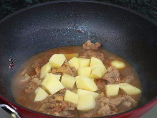 香辣土豆猪骨干锅,焖至汤汁剩下一半,倒入土豆