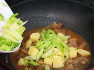 香辣土豆猪骨干锅,倒进芹菜,翻炒均匀,继续遮盖大火焖煮片刻