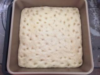 佛卡夏,发酵40分钟后,取出烤盘,用手指把面坯戳些小洞