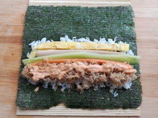 金顶寿司,在米饭上放上鸡蛋条,黄瓜,胡萝卜,火腿肠和肉松,在肉松上挤上适量的千岛酱