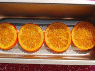 鲜橙磅蛋糕,从之前准备好的橙片糖浆中取出4片大小合适的橙片,放入模具中