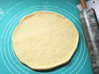 黑椒牛柳披萨,发酵好的面团,排出其中的大气泡,静置一小会后团擀成薄片,比披萨盘略大。