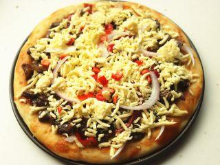 黑椒牛柳披萨,再铺上一些奶酪,表面撒一些青红椒做装饰。
