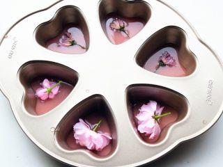樱花草莓慕斯,把用来做镜面的那部分草莓吉利丁溶液,倒一半到学厨六连心形模内,再放上一朵樱花,然后放入冰箱冷藏40分钟,等凝固。我还用了三朵盐渍樱花,盐渍樱