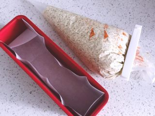 超好吃的红茶栗子磅蛋糕,搅拌好的面糊装入裱花袋中,模具内铺一层油纸。