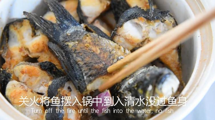 饭店绝对吃不到,这样做鱼肉超级美味下饭!,关火用洋葱块铺平砂锅,将鱼摆入锅中,倒入清水没过鱼身