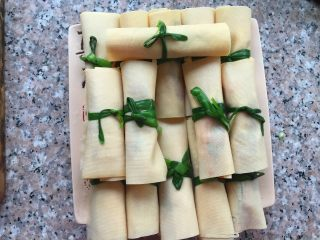 豆腐卷,用烫熟的韭菜捆起来。