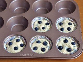 蓝莓爆浆麦芬蛋糕,将面糊舀入纸托中,上面各放四颗蓝莓。