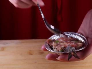 往虾里打入一颗蛋——虾扯蛋,然后借用勺子的底部,将肉馅压平。用勺子在肉馅上挖一个小的凹槽。