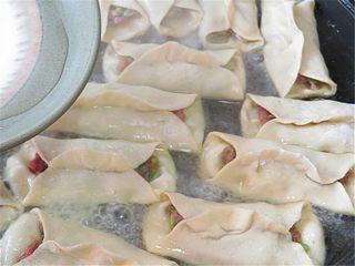 羊肉煎饺,用5克面粉加12克水调成面糊水,均匀浇在锅贴上,不会调面糊水的也可以直接用半碗水浇在锅贴上